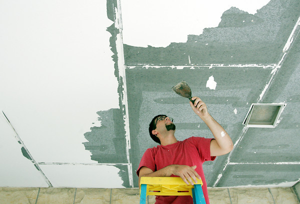Globe/Roger Nomer<br /> Clint Ames, Joplin, scrapes paint off an overhang at First United Methodist Church on Tuesday morning.  Ames was volunteering as he helped a friend with repairs around the church.