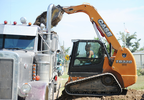 Globe/T. Rob Brown<br /> Shyann Wilson (left), bobcat operator with Camcor Environmental of Stella, removes dirt during lead remediation Tuesday afternoon, July 9, 2013, in the 2800 block of Virginia Avenue.