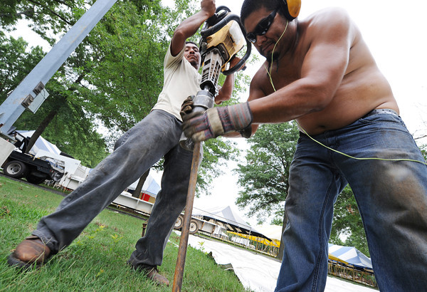 Globe/T. Rob Brown<br /> Pete Martinez (left), jackhammer operator, and David Diaz, both of Monett and with Weiser Tent Service of Monett, install stakes Monday morning, July 29, 2013, for one of about 140 tents being set up for Marian Days in Carthage.