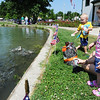 Globe/T. Rob Brown<br /> Two-year-old Shaidan Prescott (background) of Neosho and Ava'lyn Morrison, 2, of Seneca, watch trout splash around as they feed them Friday morning, July 12, 2013, during the Neosho National Fish Hatchery's 125th Anniversary Celebration.