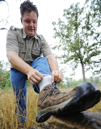 Globe/T. Rob Brown<br /> Kevin Badgley, community outreach specialist with the Missouri Department of Conservation, performs a sock tuck Friday morning, July 26, 2013, outside the Wilcat Glades Conservation & Audubon Center in Joplin. This technique makes it more difficult for ticks to crawl under clothing.