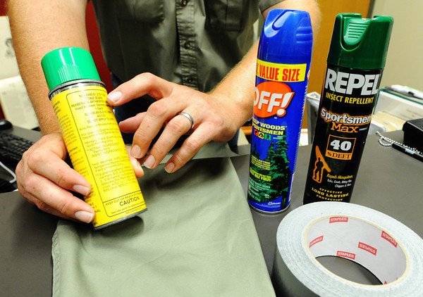 Globe/T. Rob Brown<br /> Kevin Badgley, community outreach specialist with the Missouri Department of Conservation, points out that Permethrin is the important active ingredient in insect repellent applied only to clothing for repelling ticks Friday morning, July 26, 2013, at the Wilcat Glades Conservation & Audubon Center in Joplin. He said Permethrin should not be sprayed on skin or on clothing being worn but should be sprayed on clothing exterior and allowed to dry before wearing. Other protective items shows include insect repellents with Deet, which can be sprayed on skin or clothing being worn, and duct tape for removing ticks from clothing while outdoors.