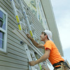 Globe/Roger Nomer<br /> Jeremy Caracci, 17, works on siding at a house near 26th and Connor on Thursday afternoon.  Caracci Tack was part of a youth group from St. Mary of Nazareth Church in Des Moines, Iowa, working with Rebuild Joplin.