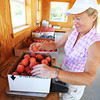 Globe/T. Rob Brown<br /> Brenda Reid, owner of Brenda's Berries, weighs a 10-pound box of peaches Friday morning, July 19, 2013, near Chetopa, Kan.