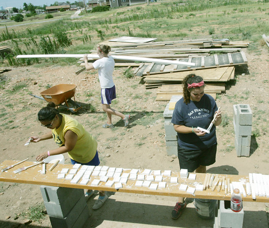 Globe/Roger Nomer<br /> (from left) Toni Saldana, Marino Valley, Calif., Abby Dockum, Des Moines, Iowa, and Lauren White, Ann Arbor, Mich., help with siding and molding at a house near 26th and Connor on Thursday.  Dockum was part of a youth group from St. Mary of Nazareth Church in Des Moines, and Saldana and White were with Catholic Mission Trips, both working with Rebuild Joplin.