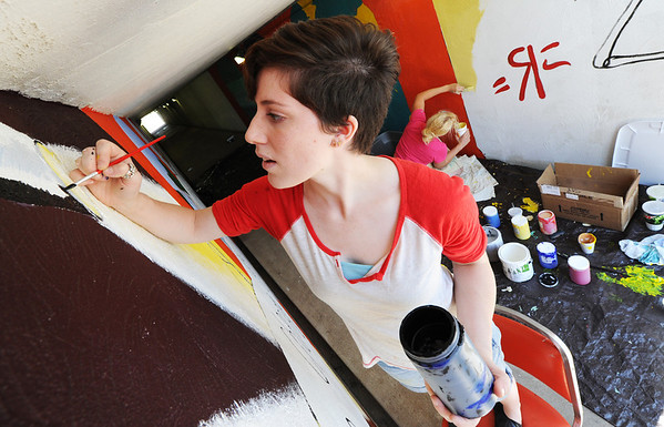 Globe/T. Rob Brown<br /> Sara Humphreys, an MSSU alumna and former art student, helps a group of art students paint a mural on the interior of the campus tunnel under Newman Road Tuesday afternoon, July 2, 2013.