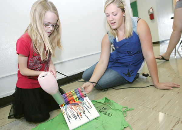 Globe/Roger Nomer<br /> Kara Bollin, 7, uses a hair dryer to melt crayons to complete her Exploding Colors Crayon Canvas with the help of Olivia Massey.  The art project was part of Art Feeds Rainbow Explosion Workshop at Irving Elementary on Thursday.