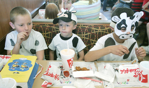 Globe/Roger Nomer<br /> (from left) Timothy Tracy, 8, Brogan, 4, and Byler Reither display their cow costumes at Chick-fil-A on Friday.  The restaurant held their annual Dress Like a Cow day, where customers received free food for dressing in costume.