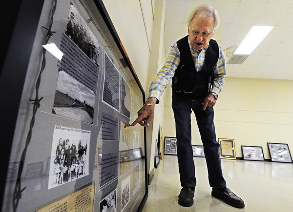 Globe/T. Rob Brown<br /> Allen Shirley of Joplin points to a piece of clothing and photos from Jewish concentration camps during World War II, part of a new Joplin Museum Complex display that unveils Saturday, Aug. 3, 2013.
