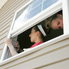Globe/Roger Nomer<br /> Bekah Akers, 16, left, and Mallorie Goodale, 17, work on window trim at a house near 26th and Connor on Thursday.  The girls were part of a youth group from St. Mary of Nazareth Church in Des Moines, Iowa, working with Rebuild Joplin.