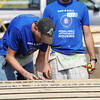 Globe/T. Rob  Brown<br /> Shane Flaherty (left) of Las Alamotis, Calif., runs a line to mark board placement as Christopher Casey of Berlin, N.J., looks on, both with Bike & Build, while working on a Habitat for Humanity home in the 2300 block of Joplin Street Tuesday morning, July 23, 2013.