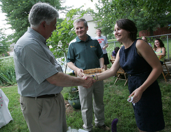 Globe/Roger Nomer<br /> Britni Stanley, Kansas City senior, shakes hands with Missouri Southern Interim President Alan Marble after getting a trip award from Chad Stebbins during an English Tea Party on Thursday for returning students who visited Europe this summer.