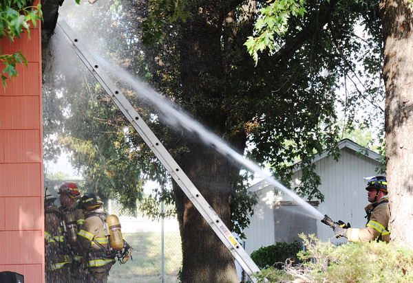 Globe/T. Rob Brown<br /> Joplin firefighters put out a fire Friday evening, July 19, 2013, in the 2000 block of Empire.
