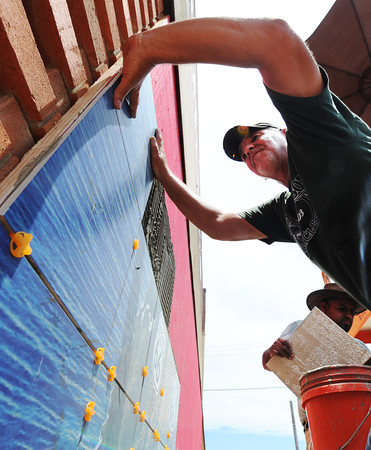Globe/T. Rob Brown<br /> Randy Wagner (above), owner of RC Tile & Hardwoods of Joplin, and installer Ricardo Solis of Carthage, install a tile mural of Route 66 Thursday afternoon, July 11, 2013, on the south side of the Pearl Bros. building near 7th and Main streets in Joplin. The mural was designed by Images In Tile.