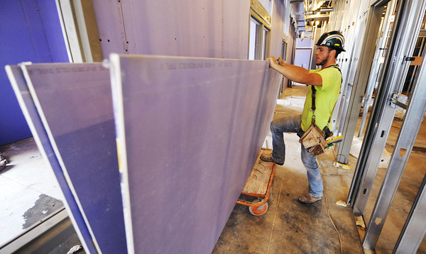 Globe/T. Rob Brown<br /> Daniel Neff of Springfield, a carpenter with Midwest Drywall of Springfield, prepares sheet rock for installation Tuesday, July 16, 2013, at the new Irving Elementary School.