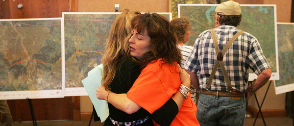 Globe/Roger Nomer<br /> Ilene Powell, left, Eureka Springs, Ark., gets a supportive hug from KJ Zumwalt, Eureka Springs, in front of maps of the proposed power lines Monday's hearing at the Inn of the Ozarks Conference Center.
