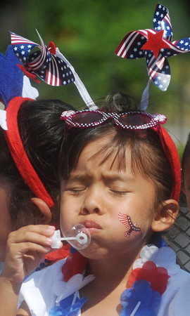 Globe/Roger Nomer<br /> Jamie Tomas, 5, takes a big breath as she blows bubbles along the parade route in Carthage on Thursday.  Area Hispanic churches organized the holiday parade.