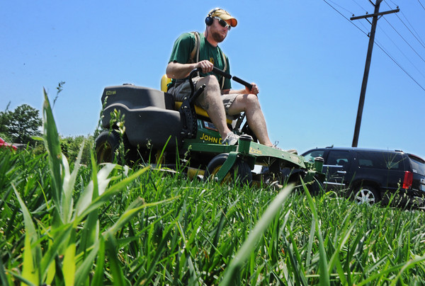 Globe/T. Rob Brown<br /> Brandon Smith of Joplin mows the lawn outside the dental offices of doctors Stephen Menke and Edward McAllister on West 20th Street Friday afternoon, July 12, 2013. Smith said, though it was hot out, it wasn't the worst day he'd ever had mowing.