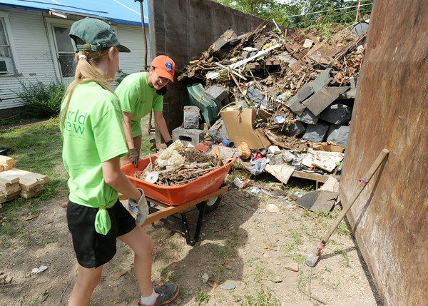 From the left: World Renew volunteers Leah Bergman, 12 and Kaylee Sartell, 12, both of Altoona, Iowa help remove debris at a tornado damaged home near 18th and Military on Wednesday in Baxter Springs.<br /> Globe | Laurie Sisk