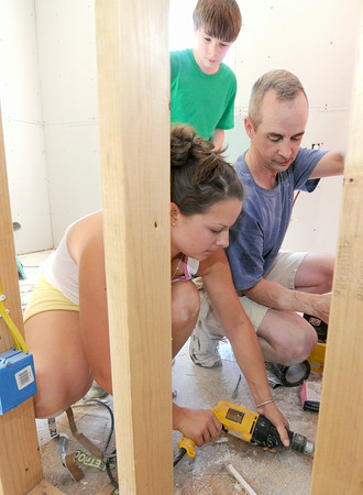 Jim Feeney, of Seekonk, Mass. and his daughter, Kayla Sylvia, of East Providence R.I. and son, Nick Feeney, 13, also of Seekonk, work to install drywall in a utility room inside a Rebuild Joplin house at 1725 Kentucky Ave. on Thursday.<br /> Globe | Laurie Sisk