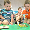 From the left: Kaleb Richards, 7, Micah Richaeds, 5 and Levi Richards, 9 decorate frames that will hold pictures of them during the Art Feeds Glow, Sparkle and Shine workshop on Saturday at St, Paul's United Methodist Church.<br /> Globe | Laurie Sisk