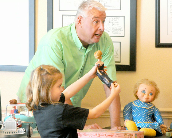 Toy collector Jay McBee gets a little assistance from five-year-old Rachel Grace Channel as he chronicles the long history of Barbie during a presentation about the history of toys on Saturday at the Webb City Historical Society.<br /> Globe | Laurie Sisk
