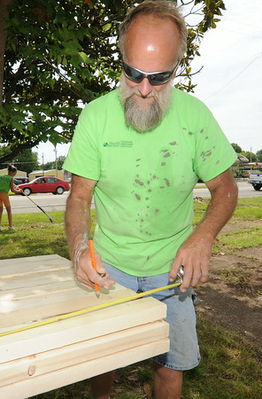 World Renew volunteer Mike Aalbers, of Prairie City, Iowa, measures boards while helping repair a house at 18th and Miltary streets in Baxter Springs on Wednesday.<br /> Globe | Laurie Sisk