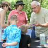 Wildcat Glades volunteer Doc Simmers, right shows Nate Yoder, 16, left, Matthew Barker, 7, center and James Barker, 5 a snake during Carver Day on Saturday at the George Washington Carver National Monument near Diamond. Also pictured is Glades volunteer Joanne Needham.<br /> Globe | Laurie Sisk