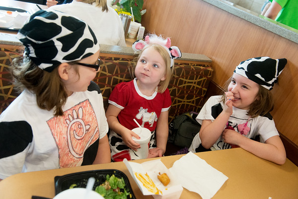 Globe/Roger Nomer<br /> Sisters (from left) Lauren, 9, Jenna, 3, and Kate, 5, Replogle, Joplin, eat at Chick-Fil-A for lunch on Tuesday during the restaurant's annual Dress Like a Cow day.