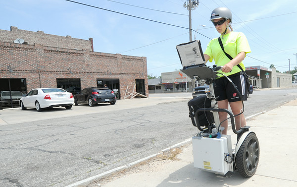 Stacey Brochtrup, an employee for Cole, uses a high-tech Segue equipped with GPS, laptop and a video camera to collect data on the condition of Joplin sidewalks near 16th and Main streets on Wednesday afternoon. The data will be presented to city officials to evaluate and prioritize future sidewalk projects.<br /> Globe | Laurie Sisk