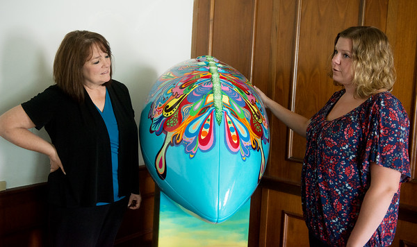 "Globe/Roger Nomer<br /> On Friday, Rebecca Brubaker, executive director, left, and Leslie Harris talks about Harris' football artwork ""New Beginnings"" which is being donated to Safehouse in Pittsburg."