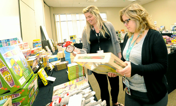 Freeman employees Cami Garrett, left and Jennifer Jones check out the large selection of children's toys at the Freeman Health System's Auxiliary Book Sale on Wednesday at the Freeman Business Center. The sale continues Thursday from 9 a.m. to 6 p.m. and Friday from 7 a.m. to 3 p.m. at Freeman West, 2W and 4W. A portion of the proceeds will go to benefit the Freeman Auxiliary.<br /> Globe | Laurie Sisk