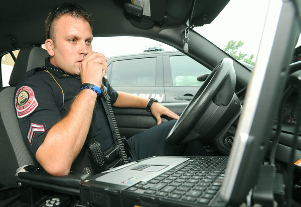 Joplin Police Department Patrol Corporal Andy Blair uses the radio in his patrol car on Thursday.<br /> Globe | Laurie Sisk
