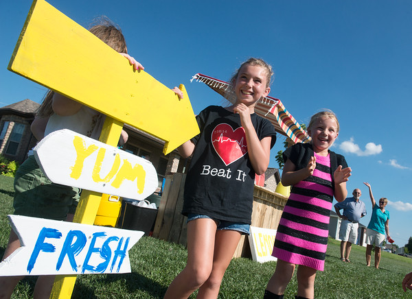 Globe/Roger Nomer<br /> Drew Yockey, 10, and Ava Sharp, 6, react on Thursday as Joplin firefighters sound their siren after visiting the Amanda Sharp lemonade stand. Yockey is a former student of Sharp, and Ava Sharp is her daughter.