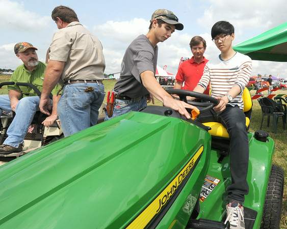Seth Stewart, center, a Pittsburg State student in the John Deere Technology program, assists Yeong Il Noh, right, from Pusan South Korea as he rides a mower for the first time in his life. Noh was accompanied Friday to the Four States Farm Show by Nico Frelogar, second from the right, an instructor in automotive technology at PSU.<br /> Globe | Laurie Sisk