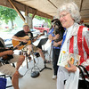 Kay Reed, Joplin, sports a red, white and blue sequined tuxedo with tails to the Webb City Farmers market o Friday as she enjoys the music of Corky Dow, left and J R Sampson, center. ### NOTE to eds: J R has no periods ..all caps and a space between J and R ###