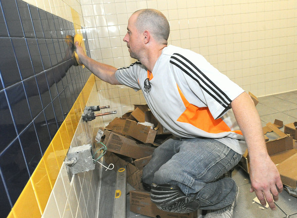 Kenneth Carter, of Galbraith Flooring, cleans freshly placed bathroom tiles at Royal Heights on Tuesday.<br /> Globe | Laurie Sisk