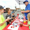 Salvation Army Youth Minister Robert Rauch and his daughter, Alli Rauch, right, teach children how to make marshmallow guns from balloons, tape and plastic cups on Saturday at the Gryphon Building parking lot. Pictured from the left: Justice Dowd, 9, Gage Pounds, 9 and Kael Pounds, 6. The event was part of the Salvation Army's 125th anniversary.<br /> Globe | Laurie Sisk