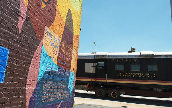 "Globe/Roger Nomer<br /> The former Kansas City Southern mail car travels past ""The Butterfly Effect"" mural in Joplin on Monday."