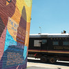 """Globe/Roger Nomer<br /> The former Kansas City Southern mail car travels past """"The Butterfly Effect"""" mural in Joplin on Monday."""