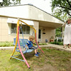 Janet Garvin and her tenant, Krystal Mahurin, right, chat outside Garvin's Lustron home as her grandson, Sam Myers, 2, plays on a swing on Thursday.<br /> Globe | Laurie Sisk