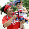 Mireya Escobar holds Zurithxi Escobar, 1, as they celebrate their faith and freedom during the Hispanic Churches Coalition Fourth of July Parade on Friday in Carthage.<br /> Globe | Laurie Sisk