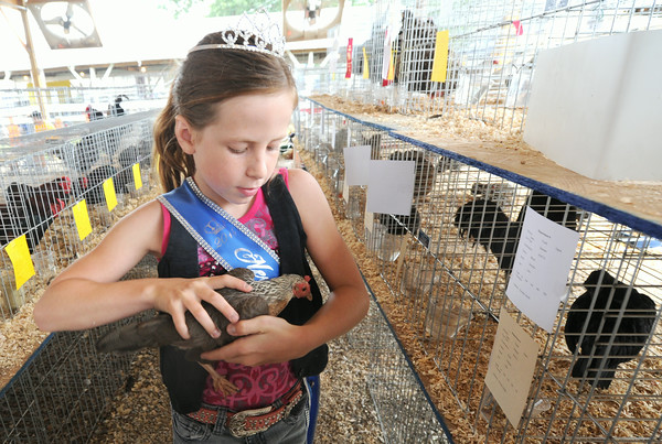 "Nine-year-old Brylee Sage holds her hen, ""Rocket"" on Thursday at the Newton County Fair. Sage was named Junior Princess at this year's fair.<br /> Globe 