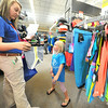 Academy Sports employee Jessica Doerr assists seven-year-old Joscelyn Larue with her back to school shopping spree on Tuesday at the store. Academy provided 30 $100 shopping sprees to members of the Joplin Boys and Girls Club.<br /> Globe | Laurie Sisk