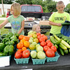 From the left: Katie Fredrickson, 10, Kallie Fredrickson, 3 and Jeremiah Jones man the Fredrickson Farms Express Booth on wednesday on Pennel street in Carl Junction.<br /> Globe | Laurie Sisk