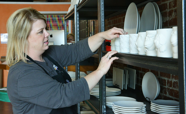 Globe/Roger Nomer<br /> Charity Hawkins, arranges dishes at Firehouse Pottery on Thursday afternoon.