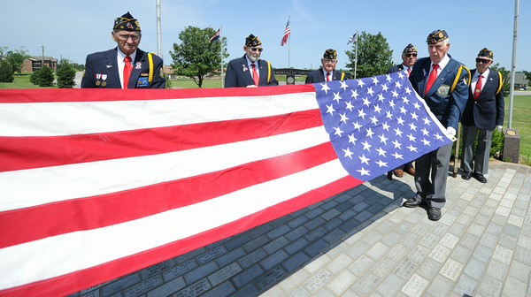 Veterans of the American Legion fold an American flag before services for a fellow veteran on Wednesday at Mount Hope Cemetery.<br /> Globe | Laurie Sisk