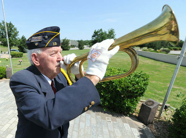 Howard Spiva practices his bugling before a veteran's memorial service on Wednesday at Mount Hope Cemetery.<br /> Globe | Laurie Sisk