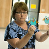 Globe/Roger Nomer<br /> Local glass artist Jane McCaulley shows some examples of her work to campers during an art project at Camp Soroptimist on Tuesday.