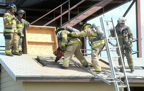 Veteran Joplin firefighters work Tuesday with new hires on ventilation traing during the third week of a four-week firefighting academy at the Carl Junction training site.<br /> Globe | Laurie Sisk